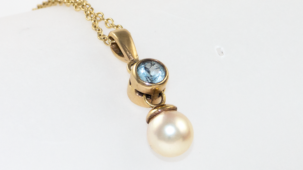 Blue topaz and a cultured pearl pendant set in 9ct yellow gold.