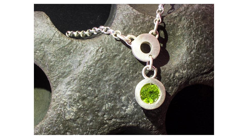 Silver symbols and shapes circle and peridot necklace