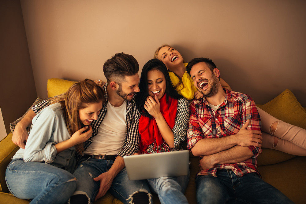 Group of friends laughing in front of computer