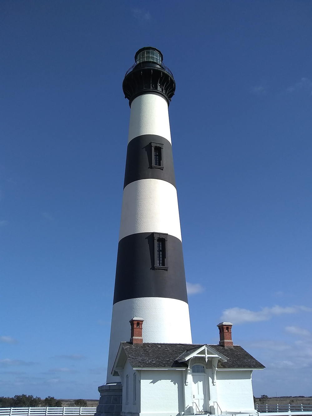 Black-and-white stripped lighthouse against a blue sky