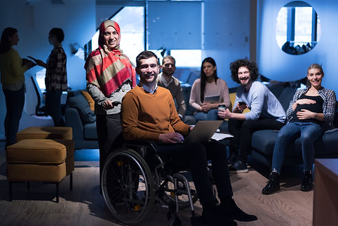 Happy, diverse, millennial work team with wheelchair user in the front
