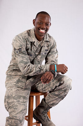 Handsome black man in a United States Air Force fatigues, sitting on a wooden stool and  l