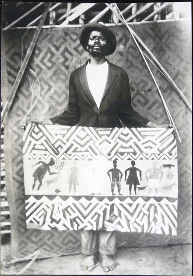 Djilatendo standing in front of a woven Kuba floor mat with one of his paintings