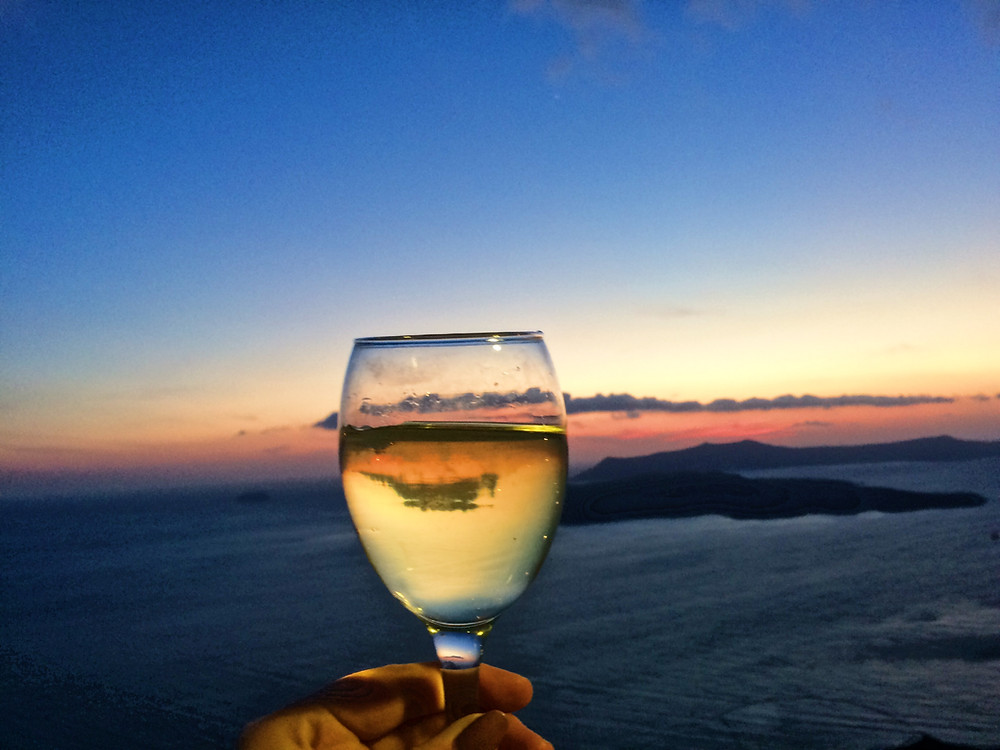 A glass of local wine and the Santorini sunset