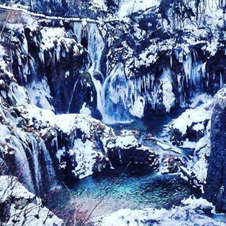 The glittering frozen waterfalls of Plitvice National Park in winter.
