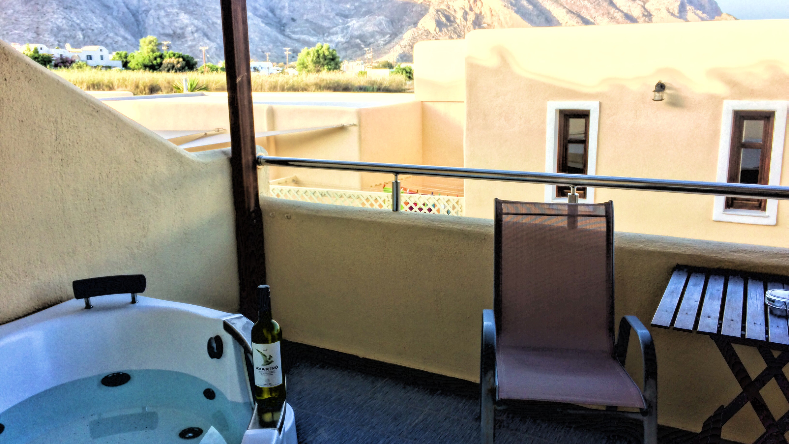 Drinking local wine in our private hot tub in Santorini, Greece. Greek island luxury.
