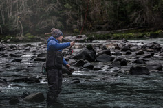 fly fisherman casts around boulder field on remote BC river