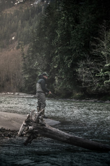 Fly fisherman standing on bank fishing remote river with old logs