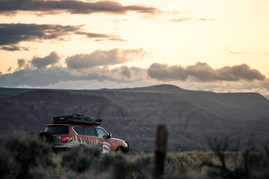 Nissan Armada Mountain Patrol Overland rig with CVT tent, Calmini bumpers, Warn winch, Nitto tires, ARB, and Rhino Rack. Offroad truck driving down into the badlands breaks