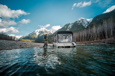 Fly fisherman loading fly rod into firefish piranha jet boat in British Columbia