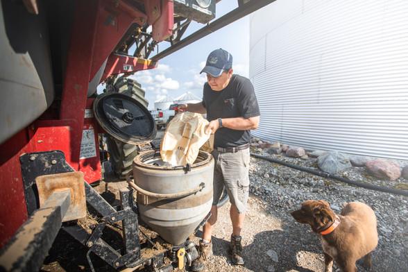 Farmer dumping fertilizer into sprayer