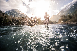 Bull trout jumping while hooked by fly fisherman in Western Canada