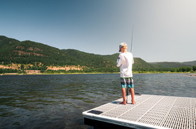 Young fisherman retying knot on his fishing pole while standing on the end of a dock in North Idaho
