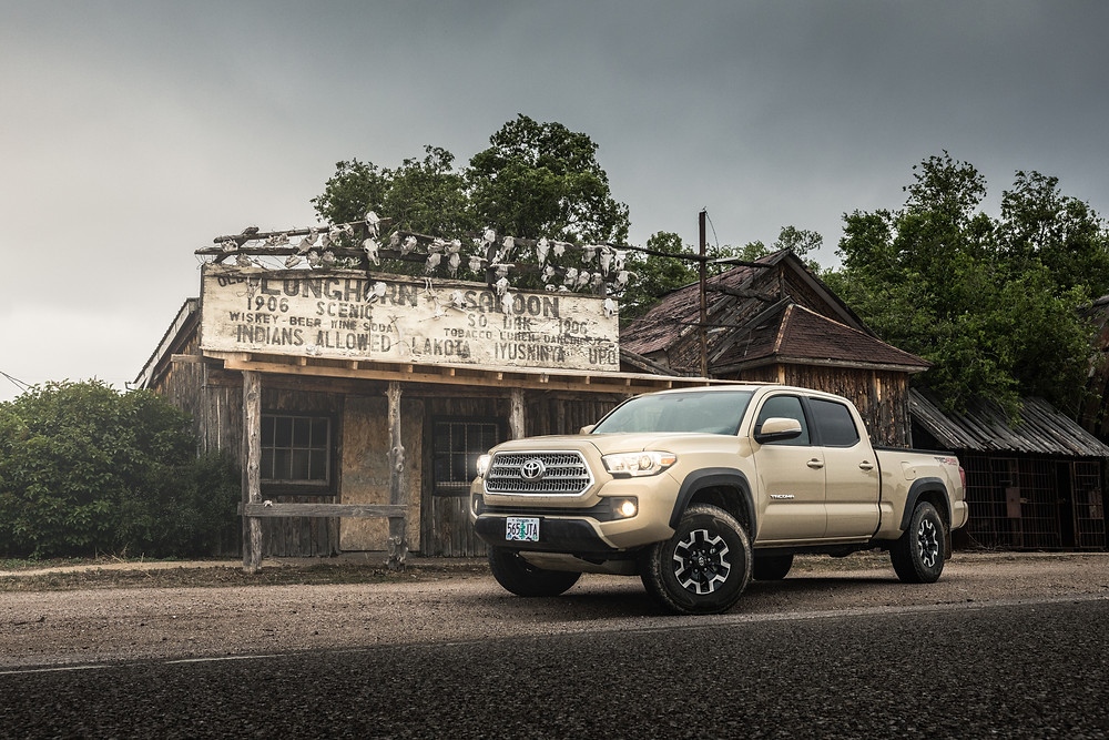 Toyota Tacoma TRD Offroad Tan at an old Ghost town in the badlands of South Dakota next to an old saloon and jail