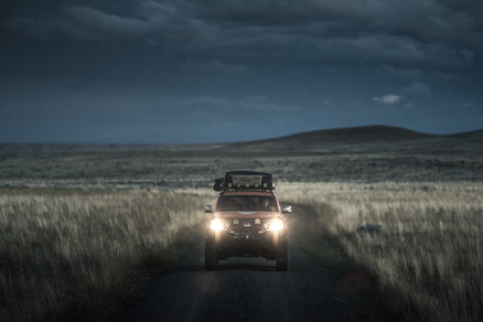 Nissan Armada Mountain Patrol Overland rig with CVT tent, Calmini bumpers, Warn winch, Nitto tires, ARB, and Rhino Rack. Offroad truck driving shot at dusk dark with headlights