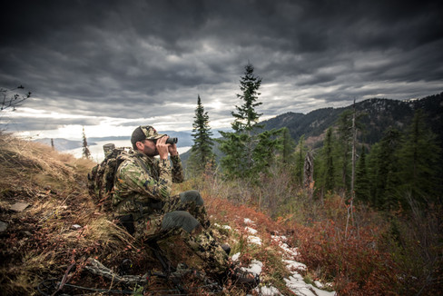 Elk hunter sits high above lake in Idaho searching for elk in the highcountry wearing sitka subalpine with mystery ranch pack and vortex razor hd binoculars