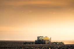 John deere air drill seeding wheat field in Central Montana in the Golden triangle durring sunset