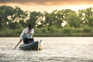 Kayaking fisherman paddles into the backlit rain on bass fishing pond in Montana