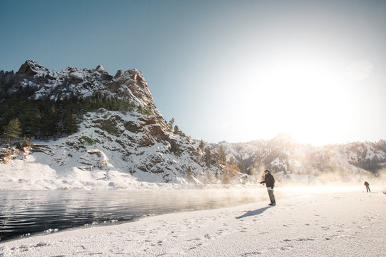 Fly fishing the missouri river in January for trout with a spey rod in hand while standing in Simms waders on an ice shelf