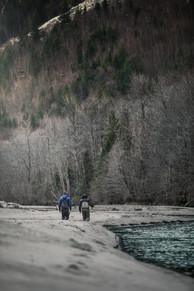 Two best friend fly fisherman walking down sandy river bank on remote fishing trip