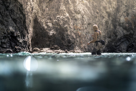 Fly fishing clear water along a steep rock wall with sun shinning down on cast
