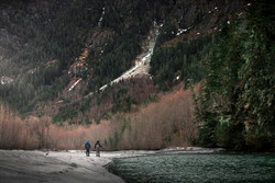 Two best friend fly fisherman walking the bank of a remote river in Western Canada in search of bull trout and cutthroat trout
