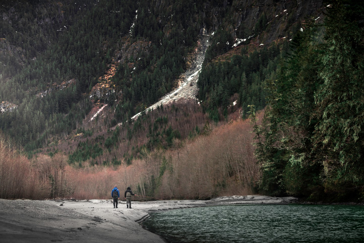 Two best friends walk down river bank while fly fishing in remote area of Canada