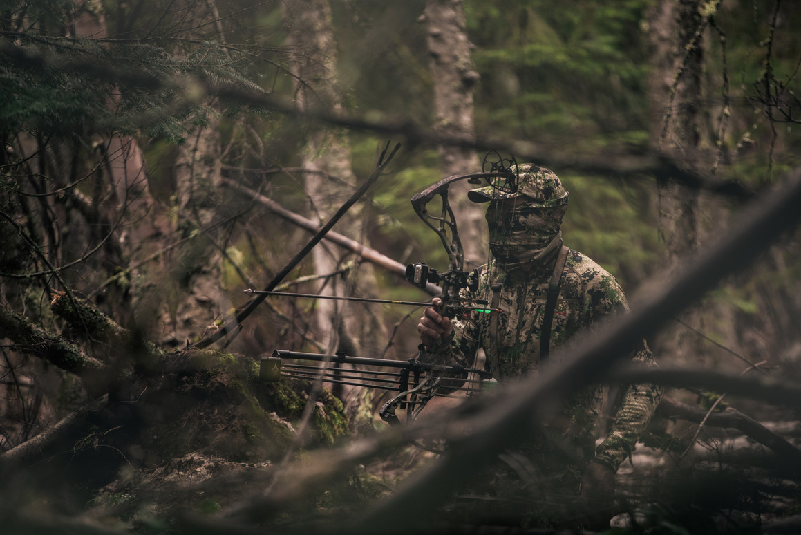 turkey hunter with nocked arrow waiting for a gobble in the thick timber in idaho