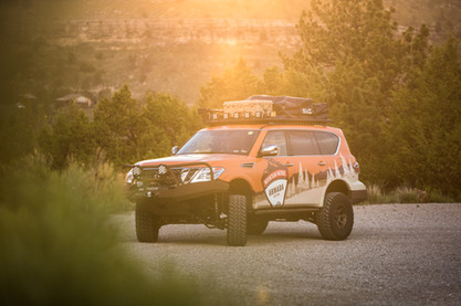 Nissan Armada Mountain Patrol Overland rig with CVT tent, Calmini bumpers, Warn winch, Nitto tires, ARB, and Rhino Rack. Offroad truck turning around on a dirt road Wyoming