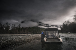 Firefish pirhana jet boat with canopy on remote river in canada with fly rods hanging out the back and fisherman stepping in the boat