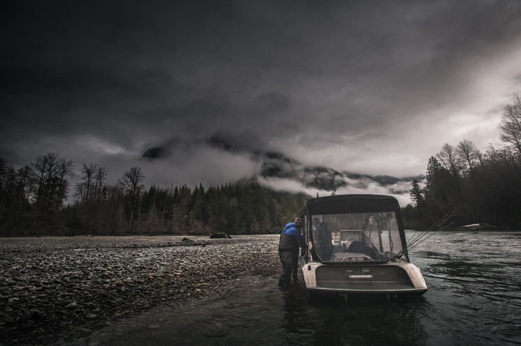 Fly fisherman loading up into Firefish Pirhana jet boat on a remote river on a cloudy dark day