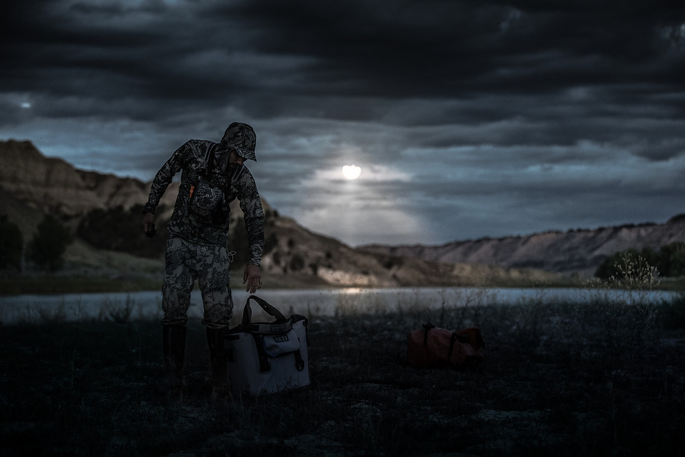 Sheep hunter drops off Yeti hopper cooler at campsite on the missouri river in the breaks