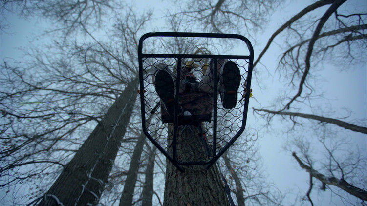 white tail hunter in treestand on cloudy day in the winter rattling horns
