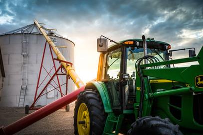 John deere tractor running grain auger for wheat harvest