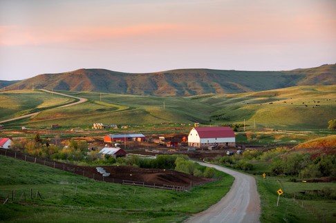 A small ranch just outside of Belt Montana along a dirt road at sunset
