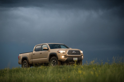 Toyota Tacoma Quicksand Tan TRD Offroad 2018 driving through grass field with storm in background