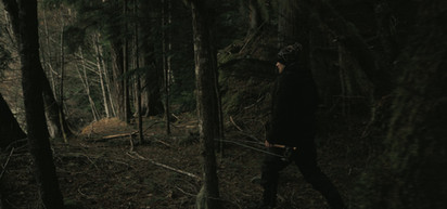 RED Raven 4.5k frame grab of a fly fisherman walking through a dark ancient forest of Vancouver islands Canada