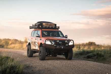 Nissan Armada Mountain Patrol Overland rig with CVT tent, Calmini bumpers, Warn winch, Nitto tires, ARB, and Rhino Rack. Offroad truck driving shot at sunset