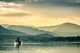 bass and pike fisherman casting off bass boat in Montana durring fire season with smoke clouds