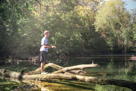Jon B. Fishing the Midwest stands on a log in his croc sandles casting a Favorite rod for small mouth on a river in Central Ohio