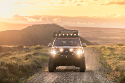 Nissan Armada Mountain Patrol Overland rig with CVT tent, Calmini bumpers, Warn winch, Nitto tires, ARB, and Rhino Rack. Offroad truck driving shot