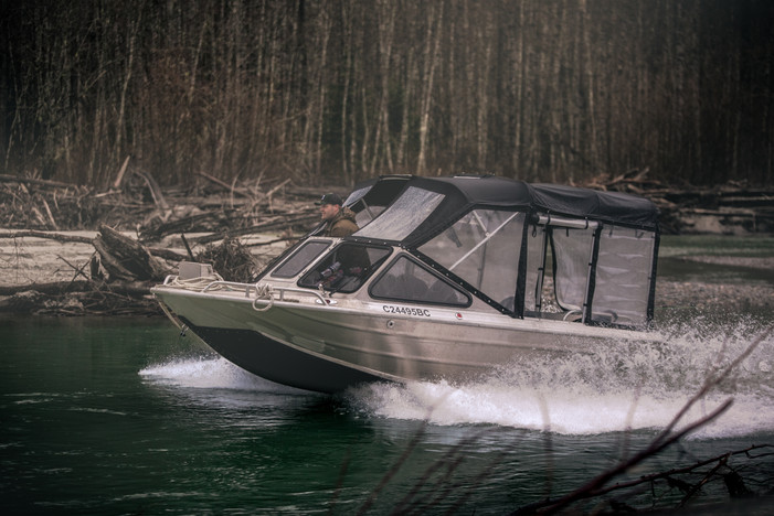 Jet boat driver running chanel on remote river in Canada in a Firefish Pirhana jet boat with canopy and UHMW bottom