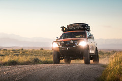 Nissan Armada Mountain Patrol Overland rig with CVT tent, Calmini bumpers, Warn winch, Nitto tires, ARB, and Rhino Rack. Offroad truck drifing corner on dirt road in Wyoming
