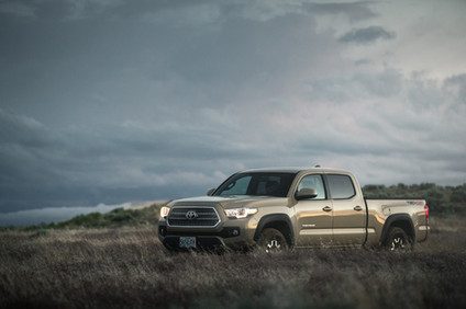 Toyota Tacoma Quicksand Tan TRD Offroad 2018 after sunset in a wild grass field of Wyoming