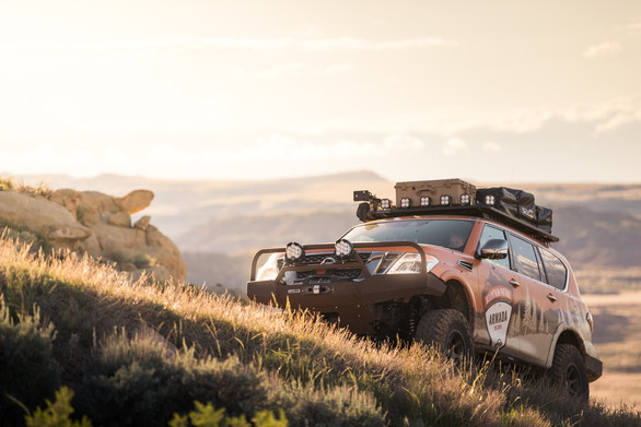 Nissan Armada Mountain Patrol Overland rig with CVT tent, Calmini bumpers, Warn winch, Nitto tires, ARB, and Rhino Rack. Offroad truck driving up hill