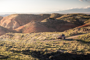 Nissan Armada Mountain Patrol Overland rig with CVT tent, Calmini bumpers, Warn winch, Nitto tires, ARB, and Rhino Rack. Offroad truck driving down ridgeline in rural wyoming