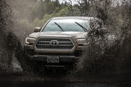 Toyota Tacoma Quicksand Tan TRD Offroad 2018 driving though dep dark mud puddle with hood and front end visable