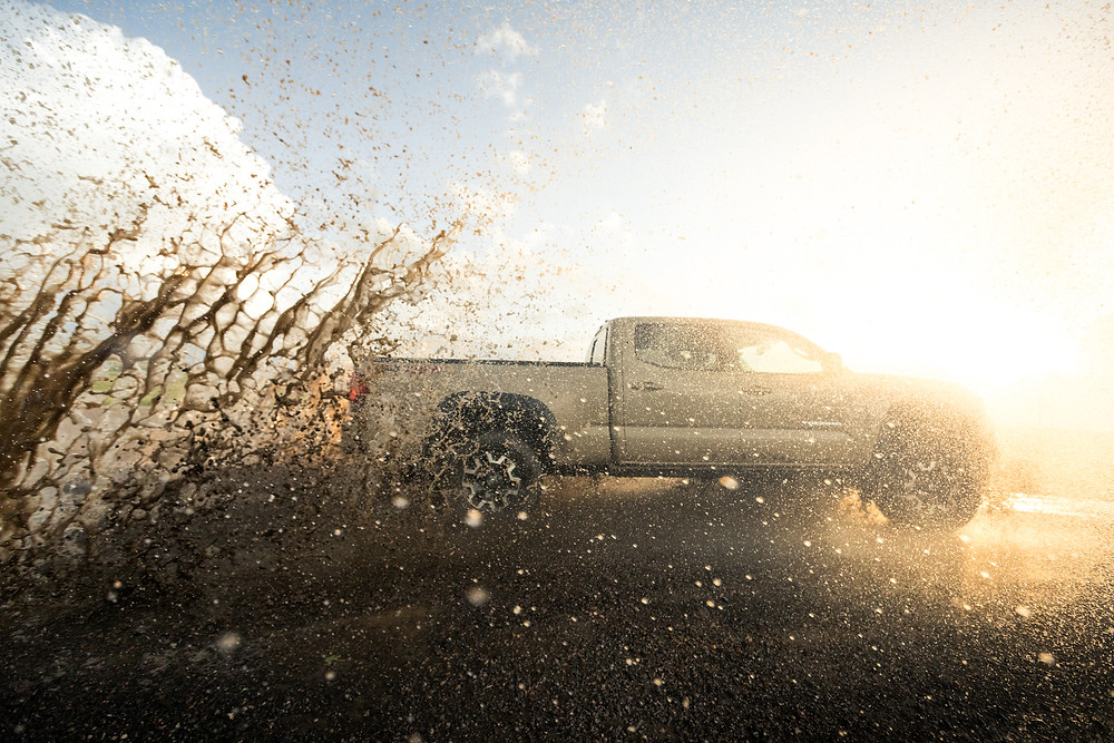 Toyota Tacoma TRD Offroad Tan splashing in mud puddle at sunset