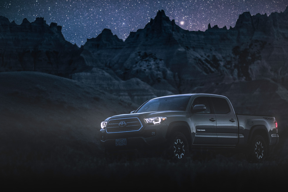 Toyota Tacoma Quicksand Tan TRD Offroad 2018 navagating the Badlands National park at night under the stars with headlights on