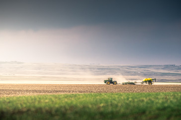 John Deere tactor pulling an air drill seeding wheat fields in Central Montana's Golden Triangle along the Missouri River breaks